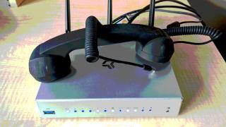 Ein Telefonhörer mit Audiostecker liegt auf einem WLAN-Router