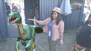 Gerendetes Dinosauriermodell, daneben Inderin