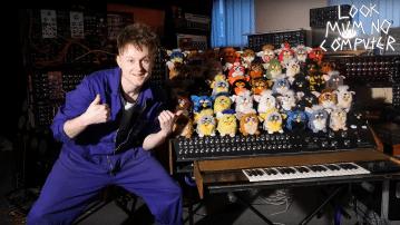 Ein weißer Mann im blauen Overall steht vor einer Orgel, auf der 44 Furbies sitzen