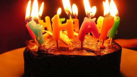 Torte mit brennenden HAPPY-Kerzen