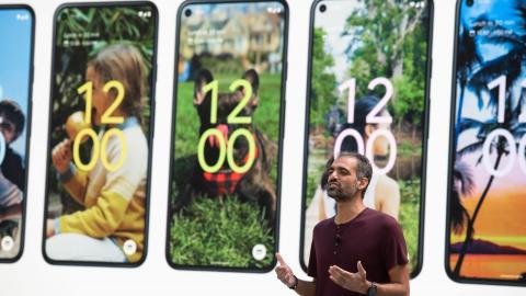 Herr Sameer Samat, hinter ihm sind auf einer Leinwand Beispiele verschiedener Handy-Sperrbildschirme zu sehen