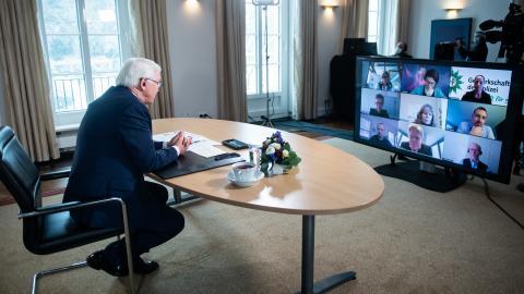 Mann sitzt alleine an ovalem Tisch, davor ein großer Bildschirm der mehrere Teilnehmer einer Videokonferenz zeigt