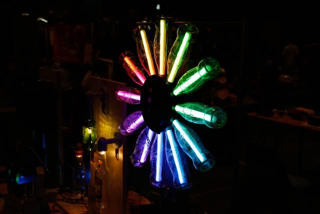 Zwölf Colaflaschen sind im Kreis angeordnet und leuchten bunt.