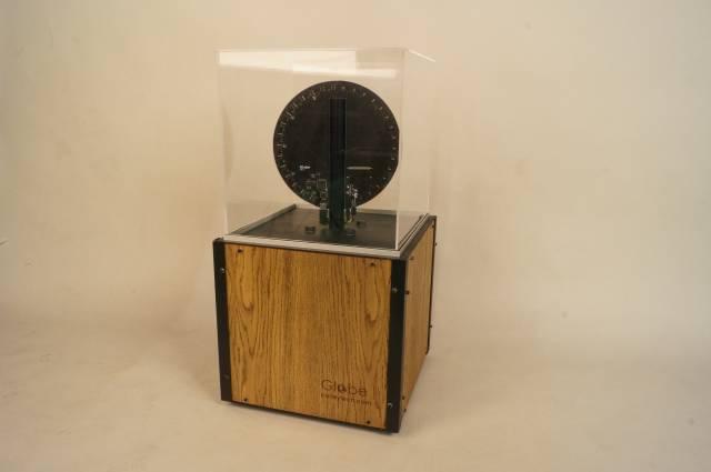 Ein Holzklotz auf dem eine schwarze Scheibe in einem Glaskäfig steht.