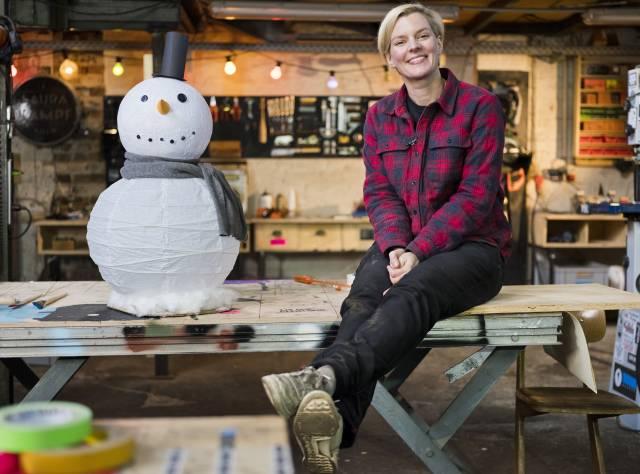 Ein Schneemann aus Pappmache sitzt neben Laura Kampf auf einem Tisch in ihrer Werkstatt.