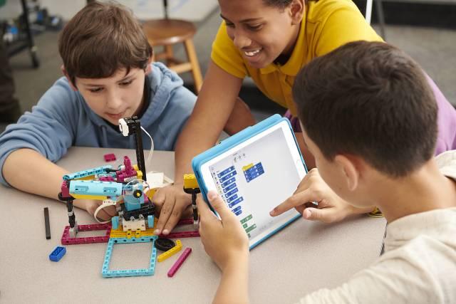 Um einen Tisch mit Lego-Teilen sitzen drei Kinder, ein Junge hält ein Tablet.