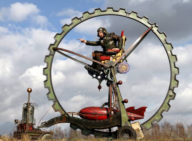 Ein Mann sitzt in einem riesigen Rad, das auf einem Gefährt befestigt ist.