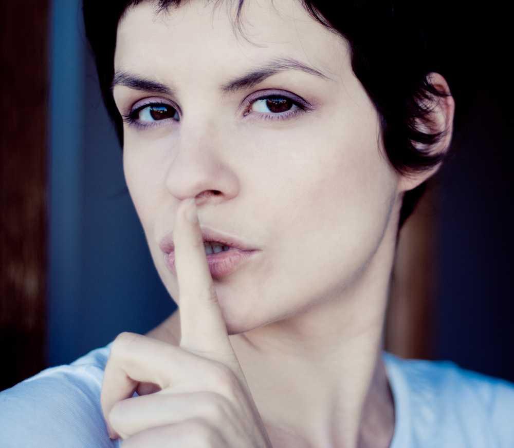 Frau legt Finger vor Mund