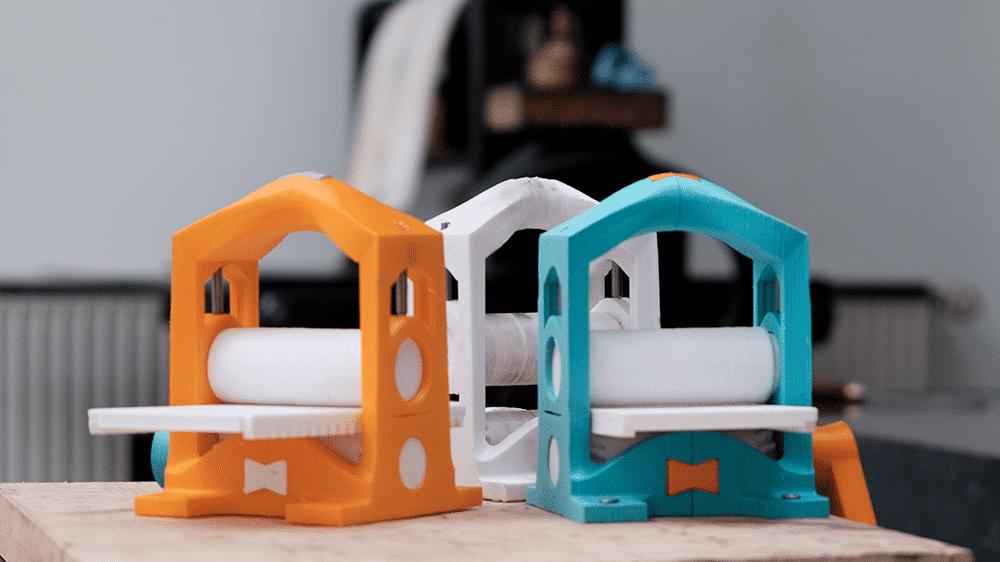 Drei kleine, bunte Druckerpressen aus dem 3D-Drucker, im Hintergrund eine große alte Presse