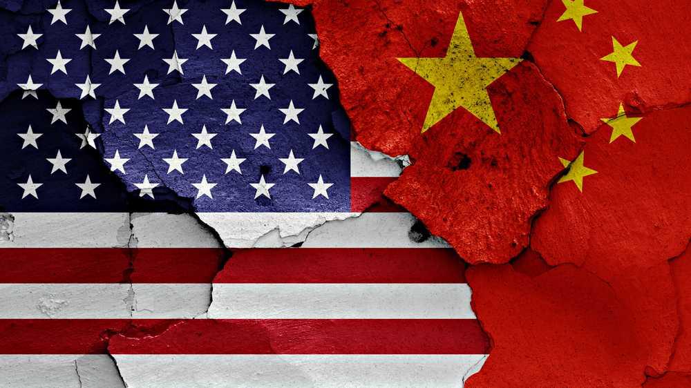 Eine Gruppe Mänchen stellt eine US-Fahne auf, die andere eine Fahne der VR China