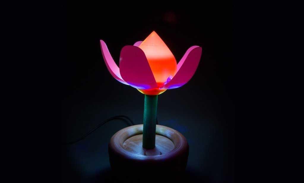 Eine bunte Blume aus dem 3D-Drucker vor dunklem Hintergrund.