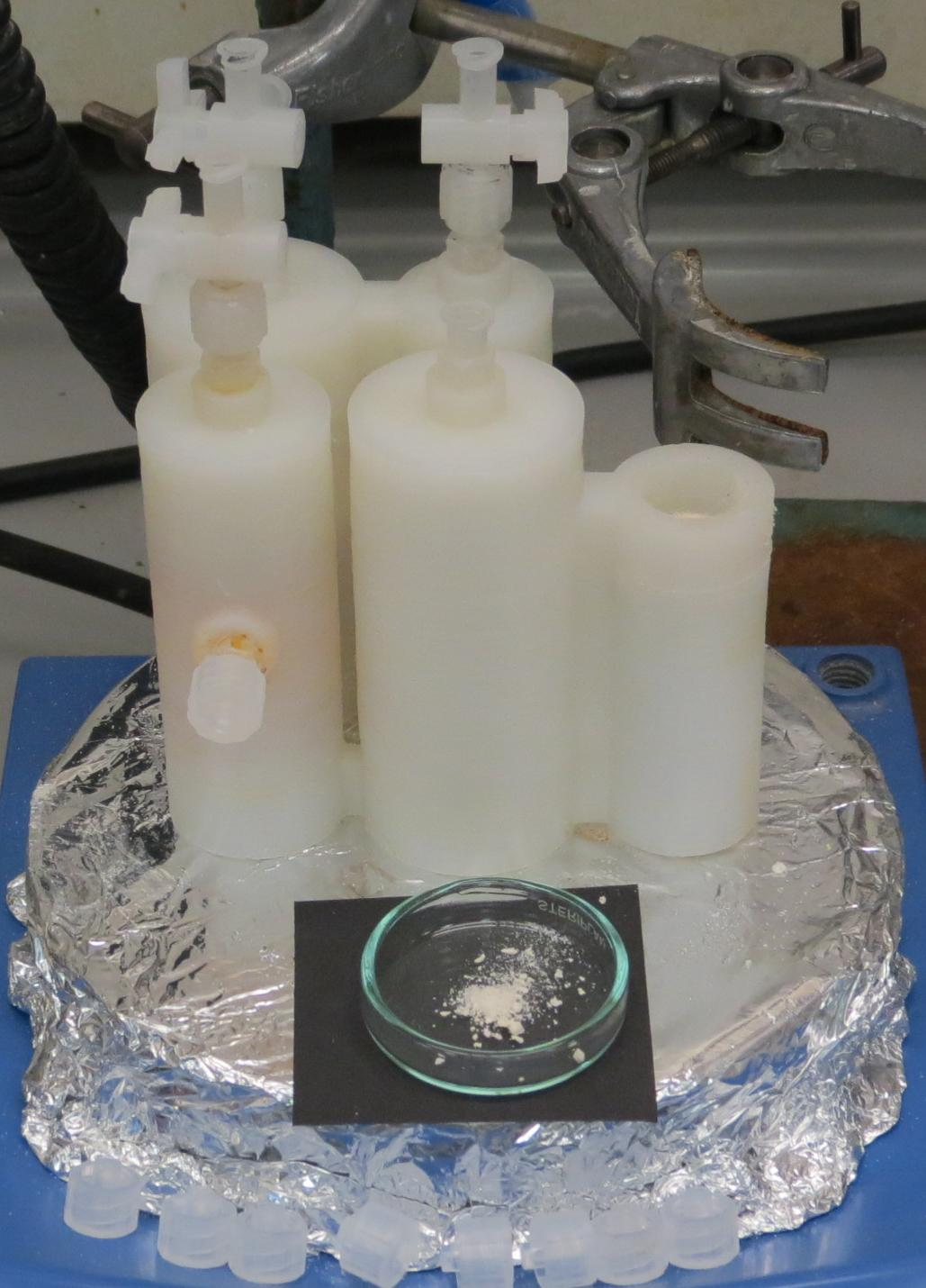 Auf einer silbernen Schale stehen mehrere weiße Zylinder, die miteinander verbunden sind. Davor liegt in einer Glasschale ein helles Pulver.