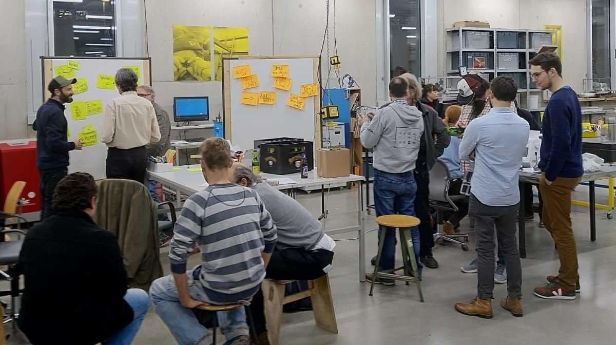 Menschen im Hafven, rund um Geräte und Flipcharts.