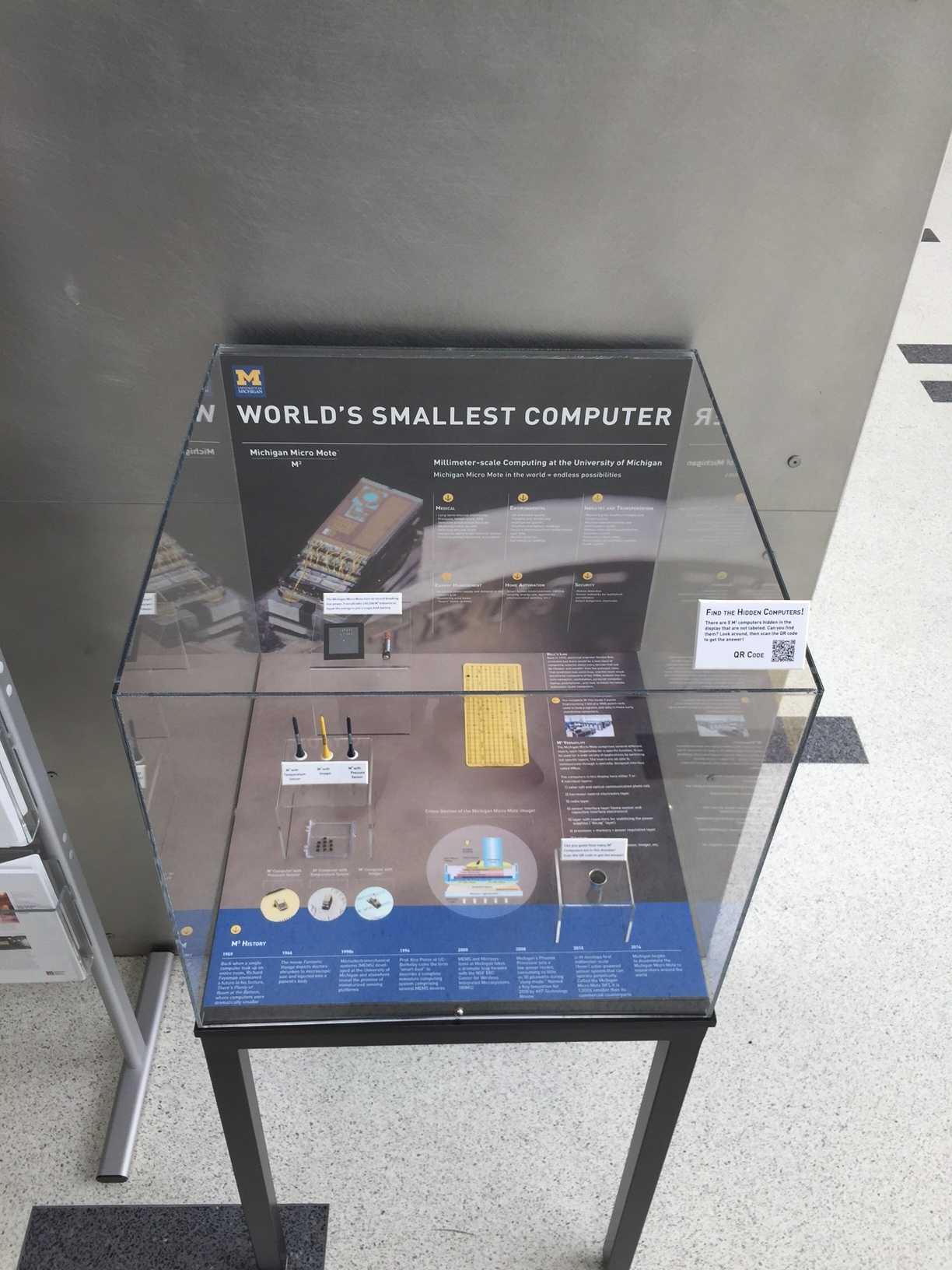 """Der winzige Computer """"Michigan Micro Mote"""" in einem Glaskasten des Computermuseums. Die gelbe Lochkarte im Hintergrund enthält einen M3 - er passt in eines der ausgestanzten Löcher."""