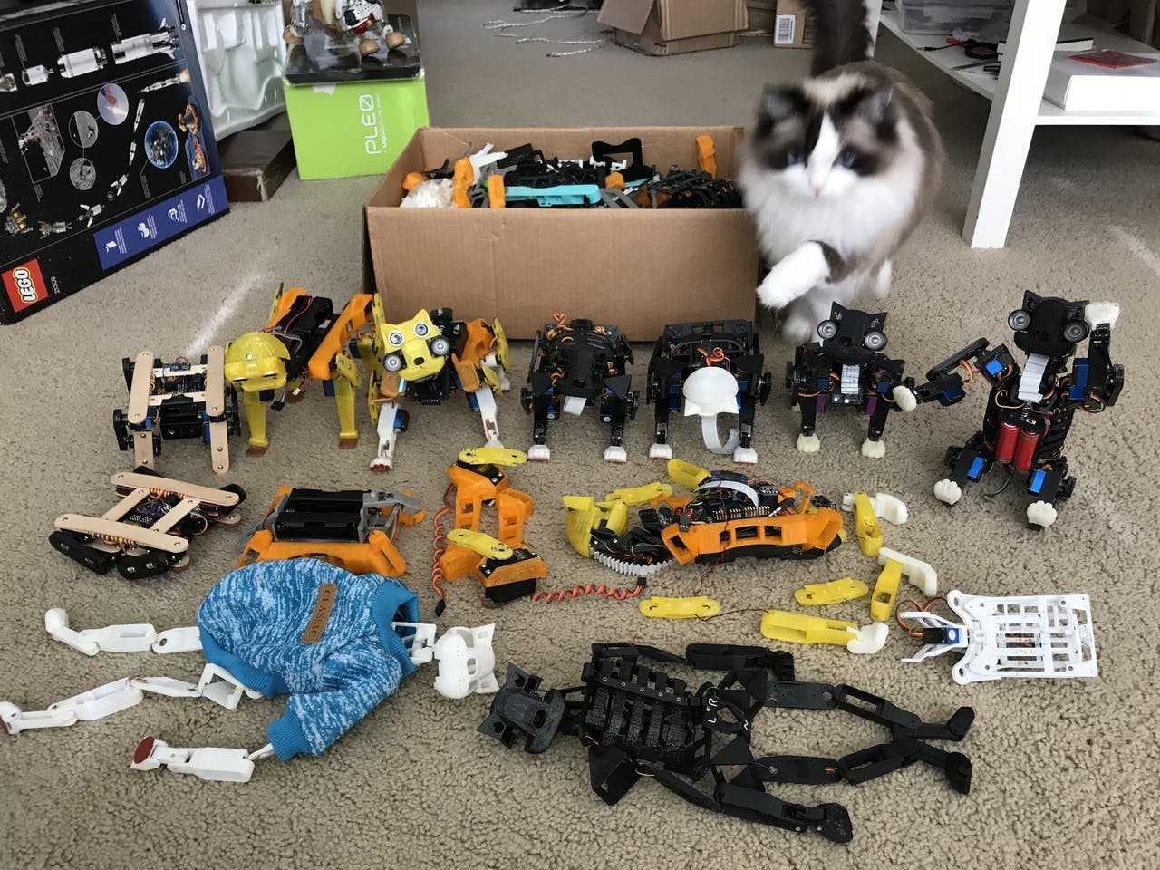 Eine Katze sitzt neben Elektronikkomponenten und Teilen aus dem 3D-Drucker