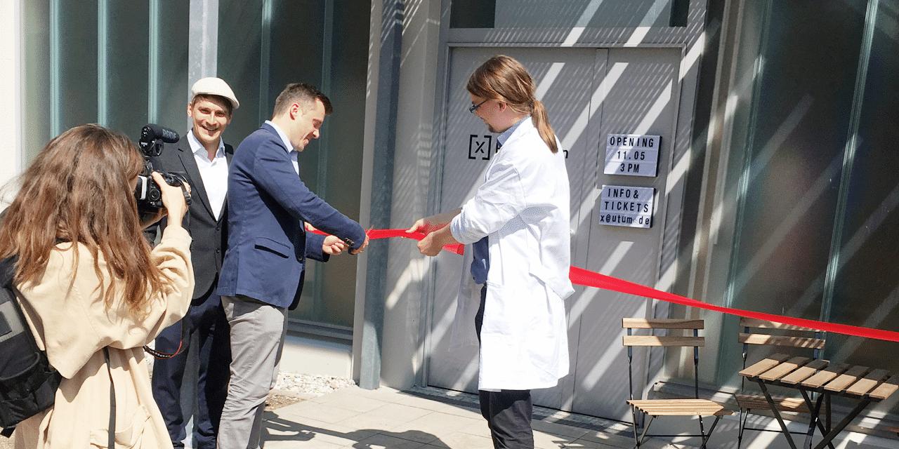 Eröffnung der Bio.kitchen in München mit feierlichem Zerschneiden des roten Bands vor der Labortür