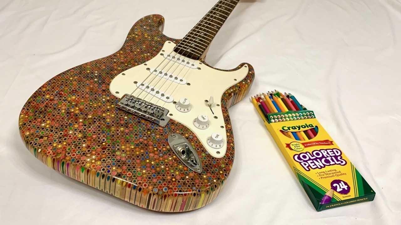 Gitarre mit Körper aus Buntstiften neben einer Buntstiftpackung