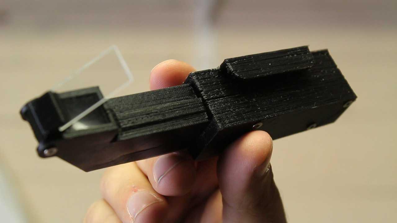Eine Hand hält ein 3D-gedrucktes Teil mit Linse hoch.