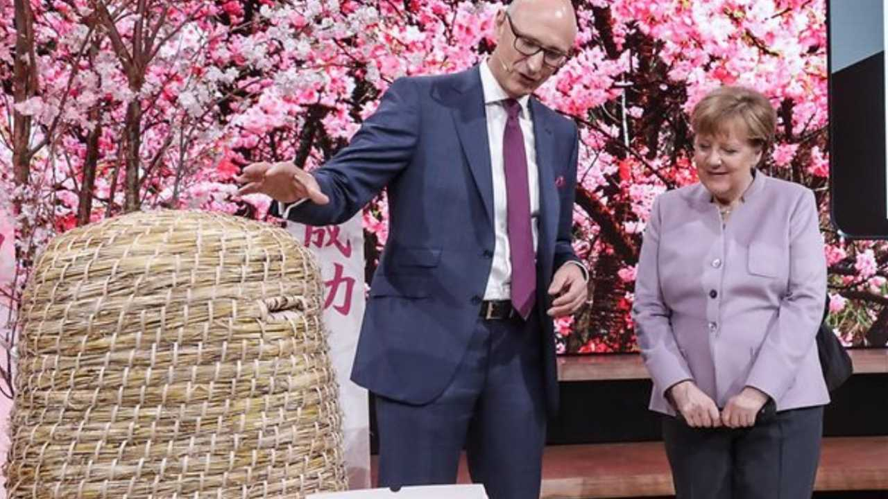 Telekom-Chef Timotheus Höttges zeigt Bundeskanzlerin Angela Merkel, wie er Bienen helfen möchte