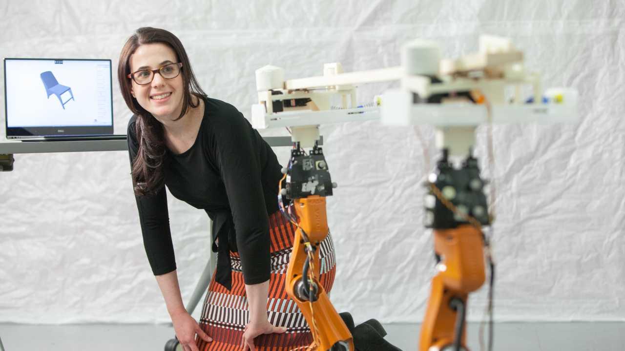 Eine junge Frau beugt sich neben einem Schreibtisch nach vorn und schaut zwei Roboterarme an, die ein Stück Holz halten