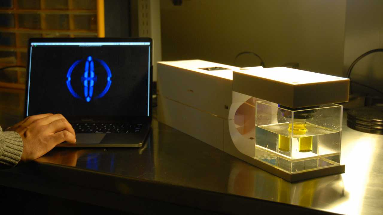 Ein neuartiger 3D-Drucker steht neben einem aufgeklapptem Laptop.