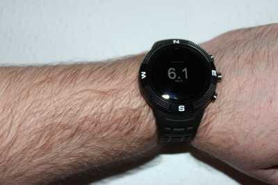 Eine Arm, der eine schwarze Smartwatch am Handgelenk trägt. Auf dem Display steht: 6,1 km/h.