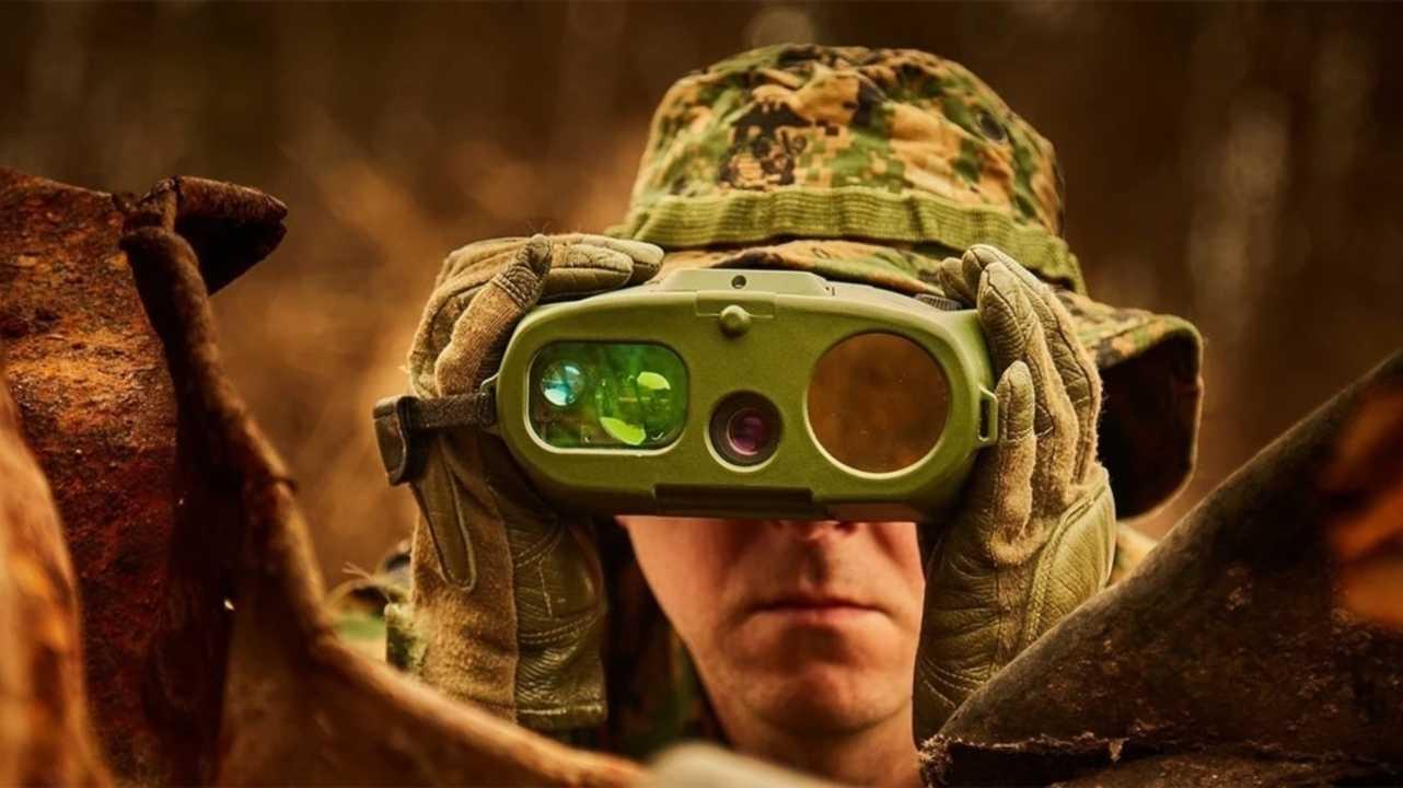Mann in Tarnkleidung mit Überwachungs-Fernglas