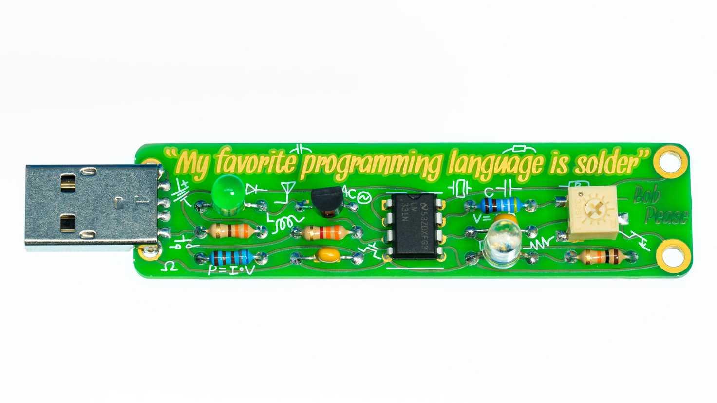 """Grüner USB-Stick von Boldport mit aufgelötetem Bauteilen und der Aufschrift """"My favourite programming language is solder""""."""
