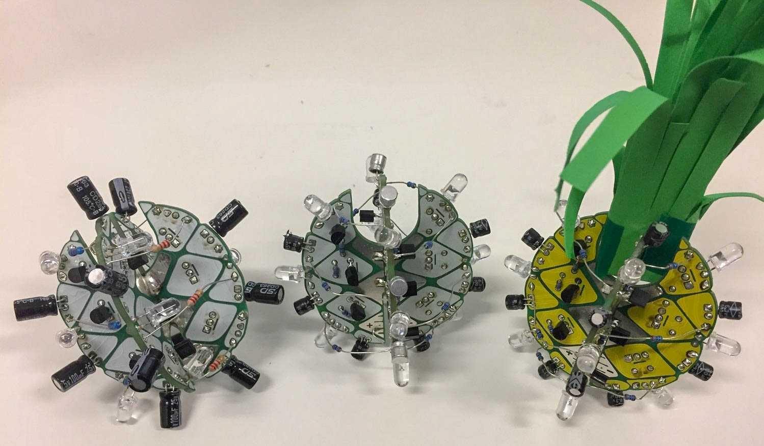 Drei Projekte aus zwei verschränkten Boards und aufgelöteten Komponenten, eines davon mit gelbem PCB und aufgestecktem Grün - wie eine Ananas.