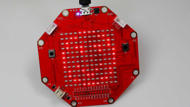 sino:bit - eine achteckige rote Platine. Auf der 12x12-LED-Matrix leuchtet ein Smiley