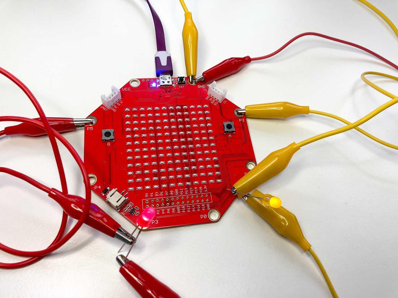 Sinobit mit angeschlossenen Kabeln, an denen zwei LEDs hängen