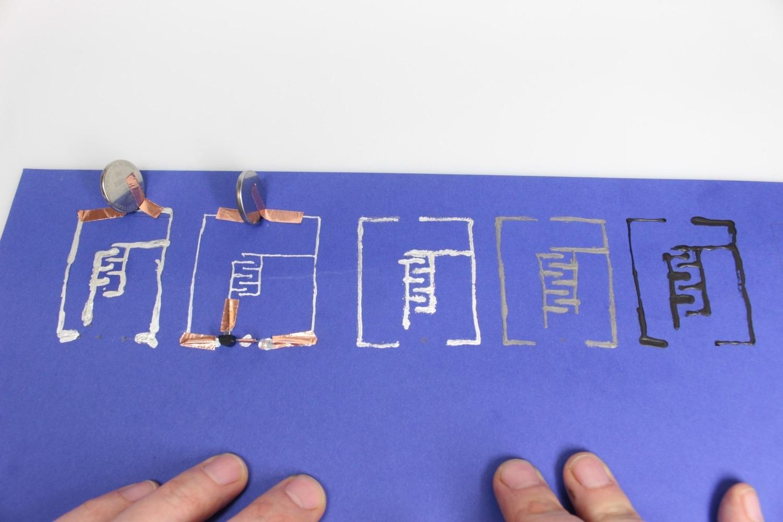 Ein blaues Blatt Papier mit verschiedenen leifähigen Tinten