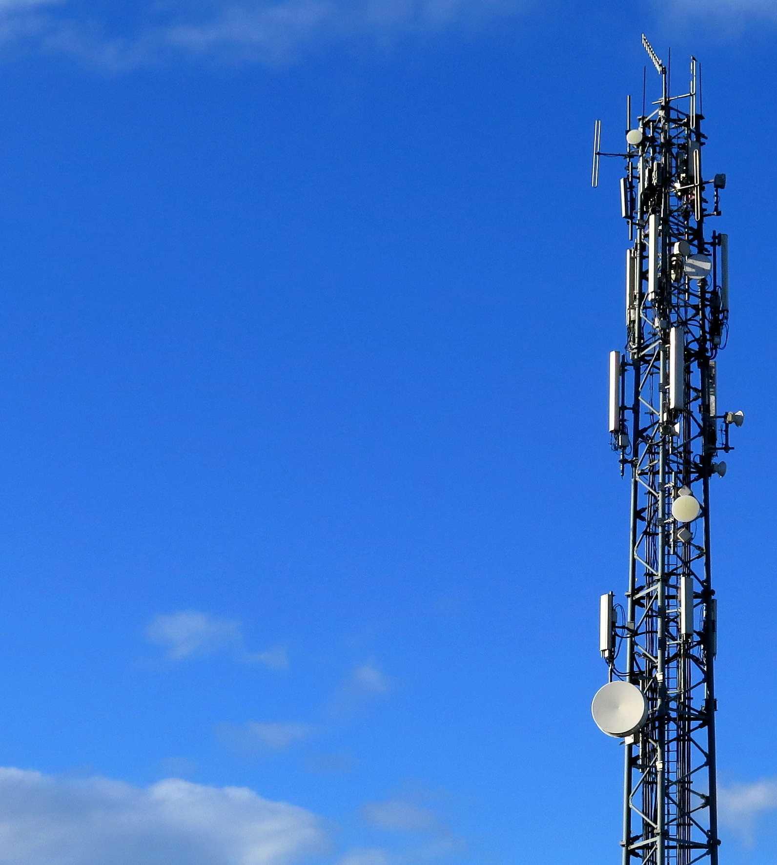 Mast mit vielen Antennen vor blauem Himmel