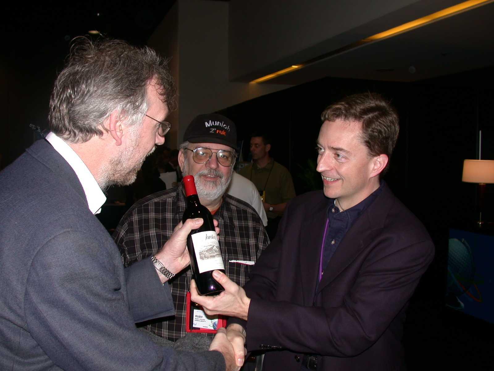 """Intel CTO Pat Gelsinger überreicht auf dem IDF 2002 vor den Augen von Journalisten-Urgestein Rudy Kulzer vom Handelsblatt seine Wettschuld.  Die Krzanich-Nachfolge hat er jetzt """"abgetwittert"""""""