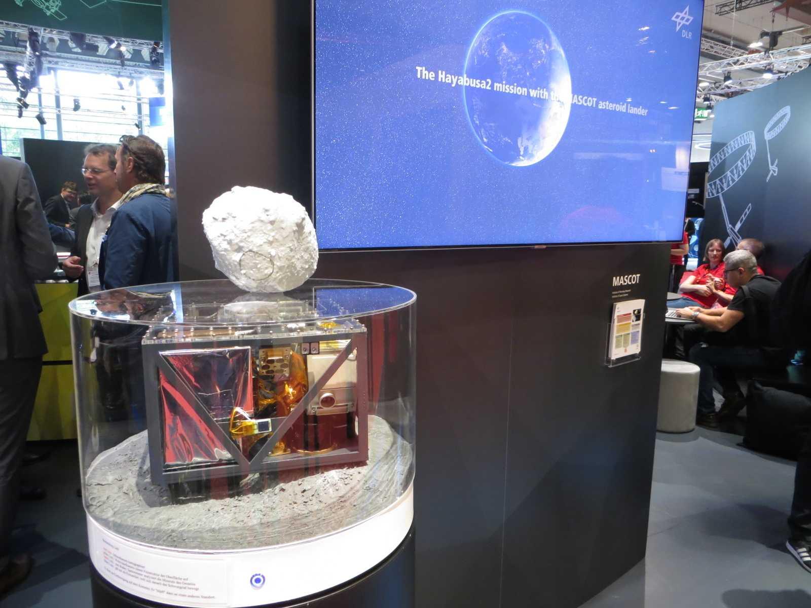 Am Stand des DLR lässt sich an diesem Modell des Landers Mascot (Originalgröße) nachvollziehen, wie die Sensoren und die Sprungtechnik arbeiten. Auf dem Modell von Ryugu ist mit einem schwarzen Kreis das Landegebiet markiert.