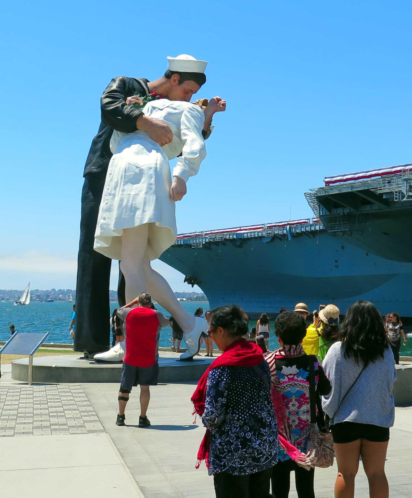 Touristen, dahinter eine riesige Statue: Matrose küsst Mädchen