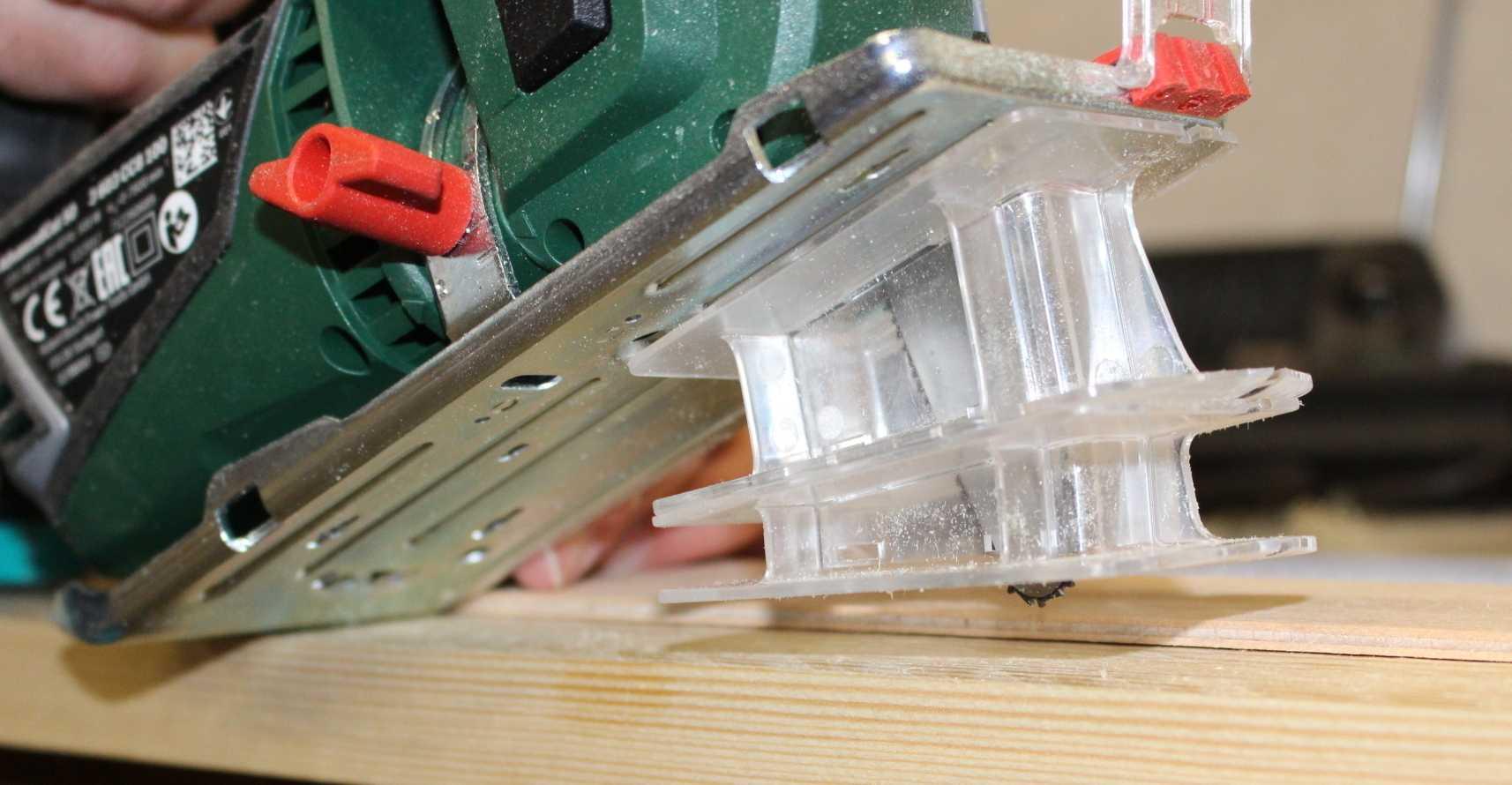 Unter einer grünen Kettensäge sind zwei durchsichtige Plastikeinsätze eingeklemmt.