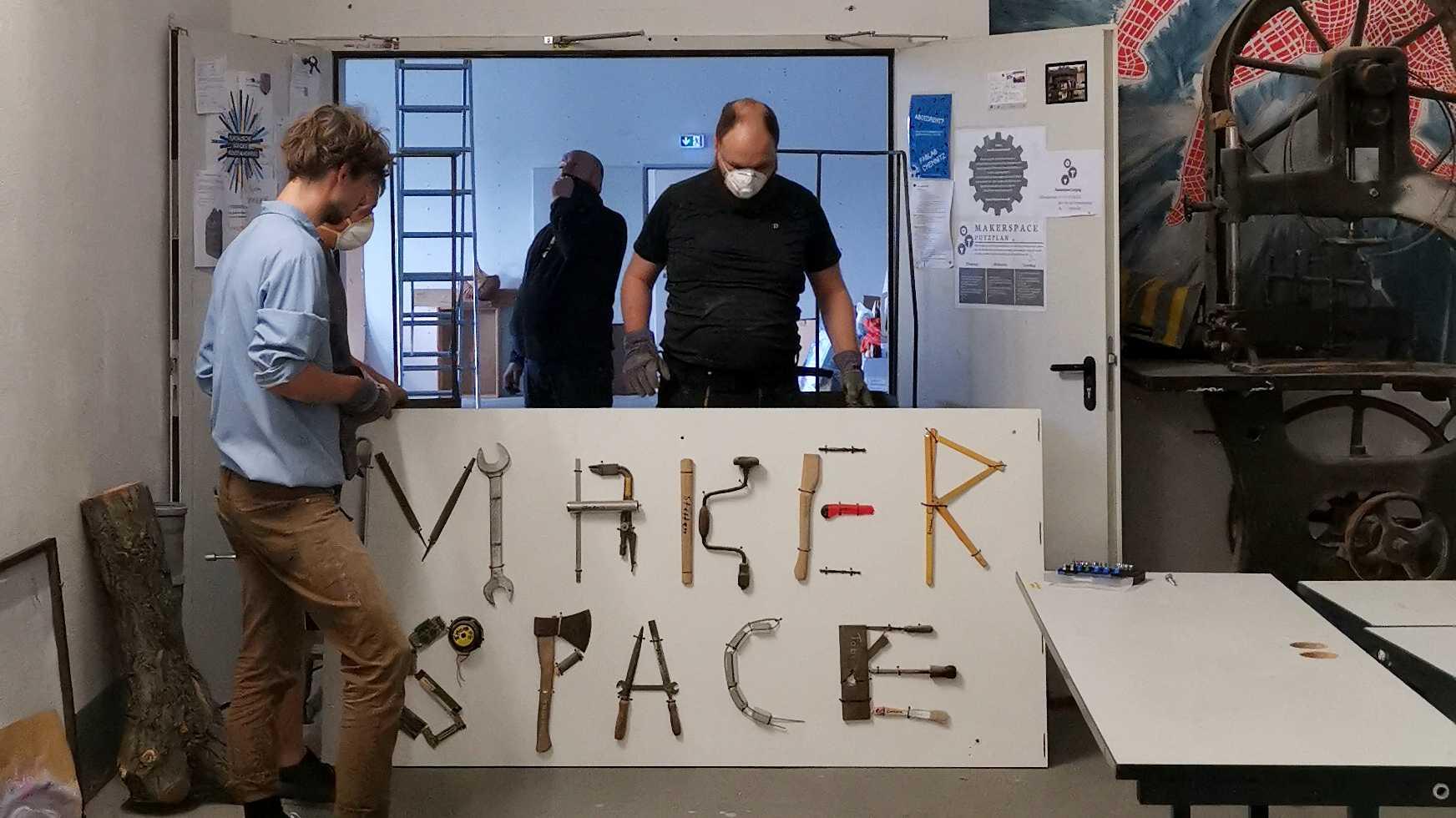 """In einer Tür stehen vier Menschen um ein Schild mit der Aufschrift """"Makerspace""""."""