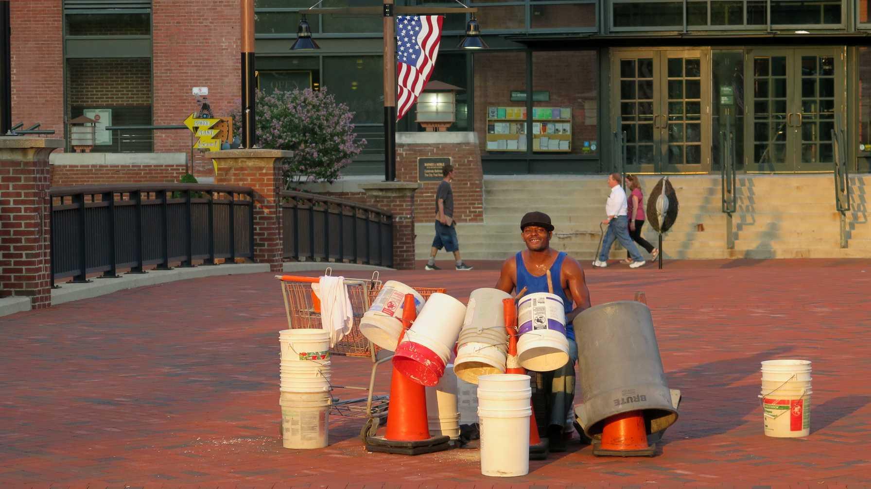 Musikant mit Schlagzeug aus Plastikkübeln