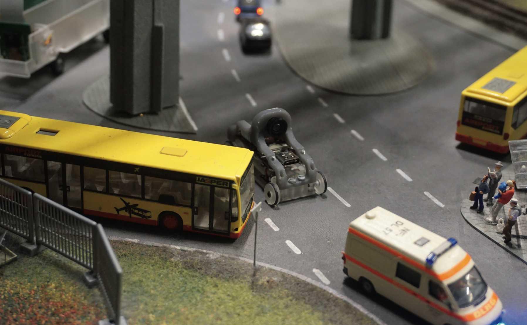 Visuelle Navigation im Maßstab 1 zu 87: Ein Minifahrzeug mit Raspi-Steuerung und Kameramodul zwischen Modellautos im Hamburger Miniatur-Wunderland.