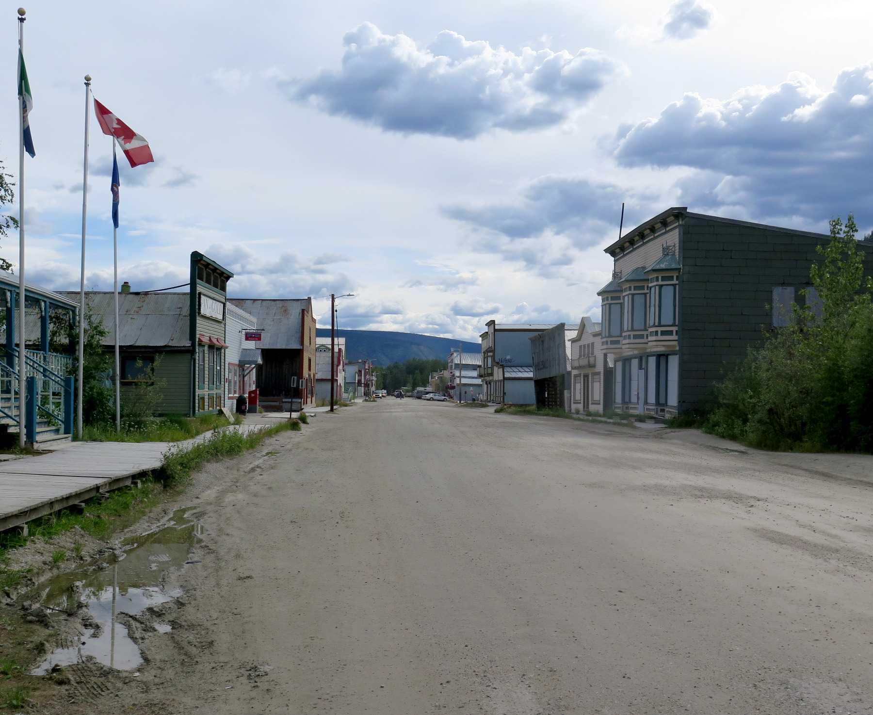 Ungeteerte Straße, links und rechts Holzhäuser