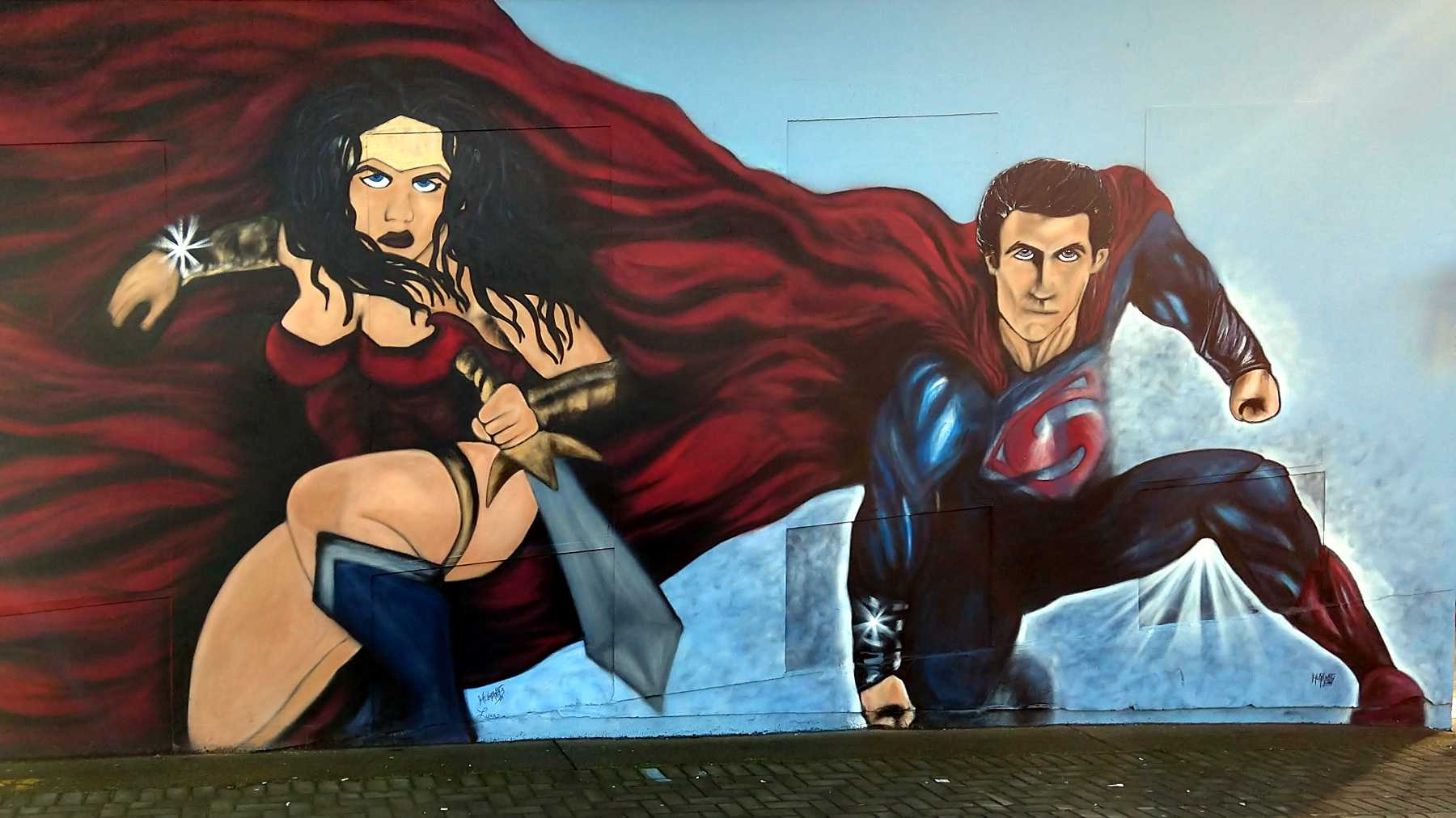 Straßenkunst Gemälde mit Superwoman und Superman