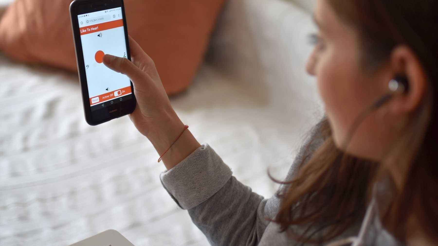 Eine junge Frau mit Kopfhörern schaut auf die liketohear-App.