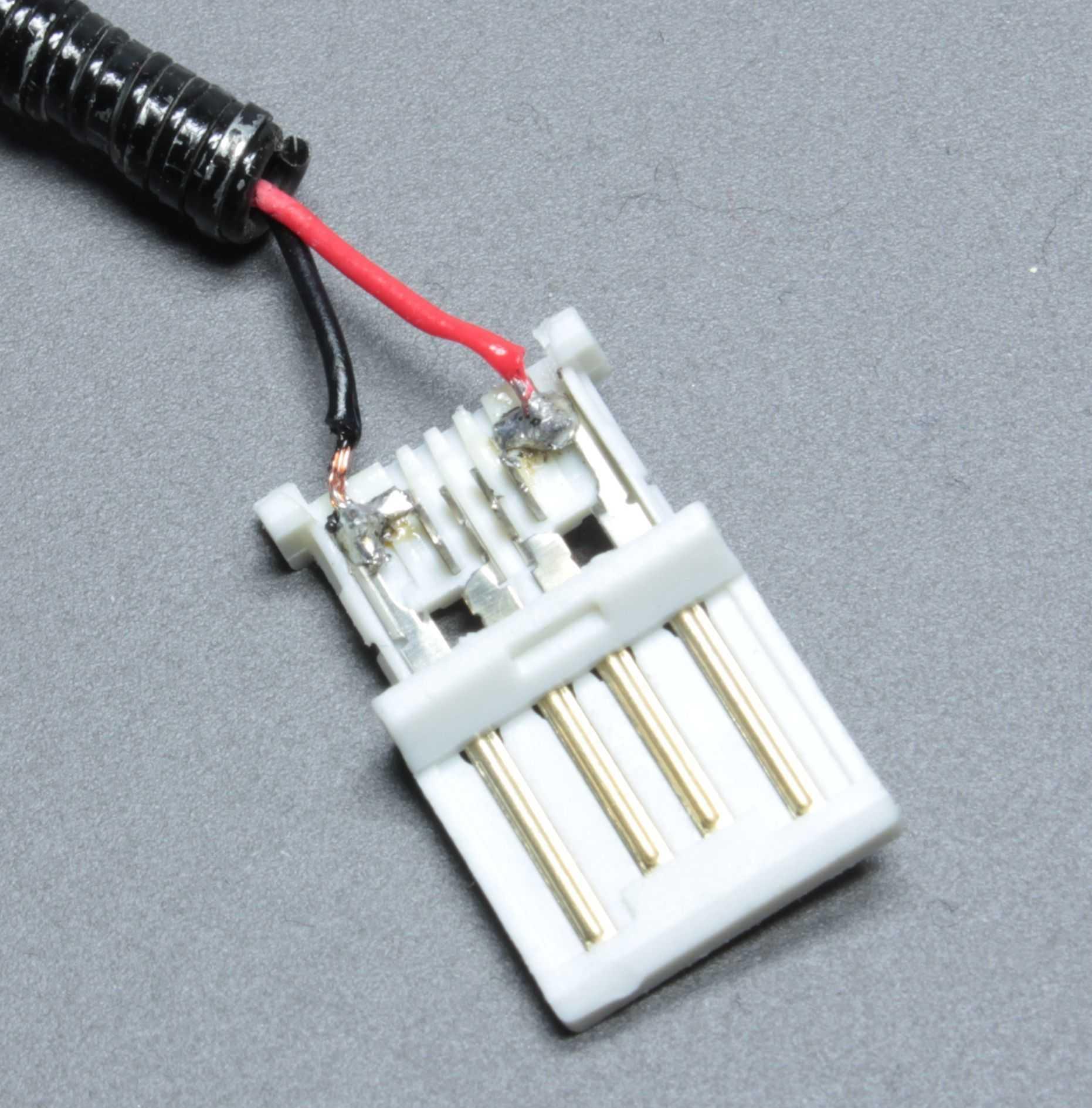 USB-Stecker: eine weiße Platine mit rotem und schwarzen Kabel