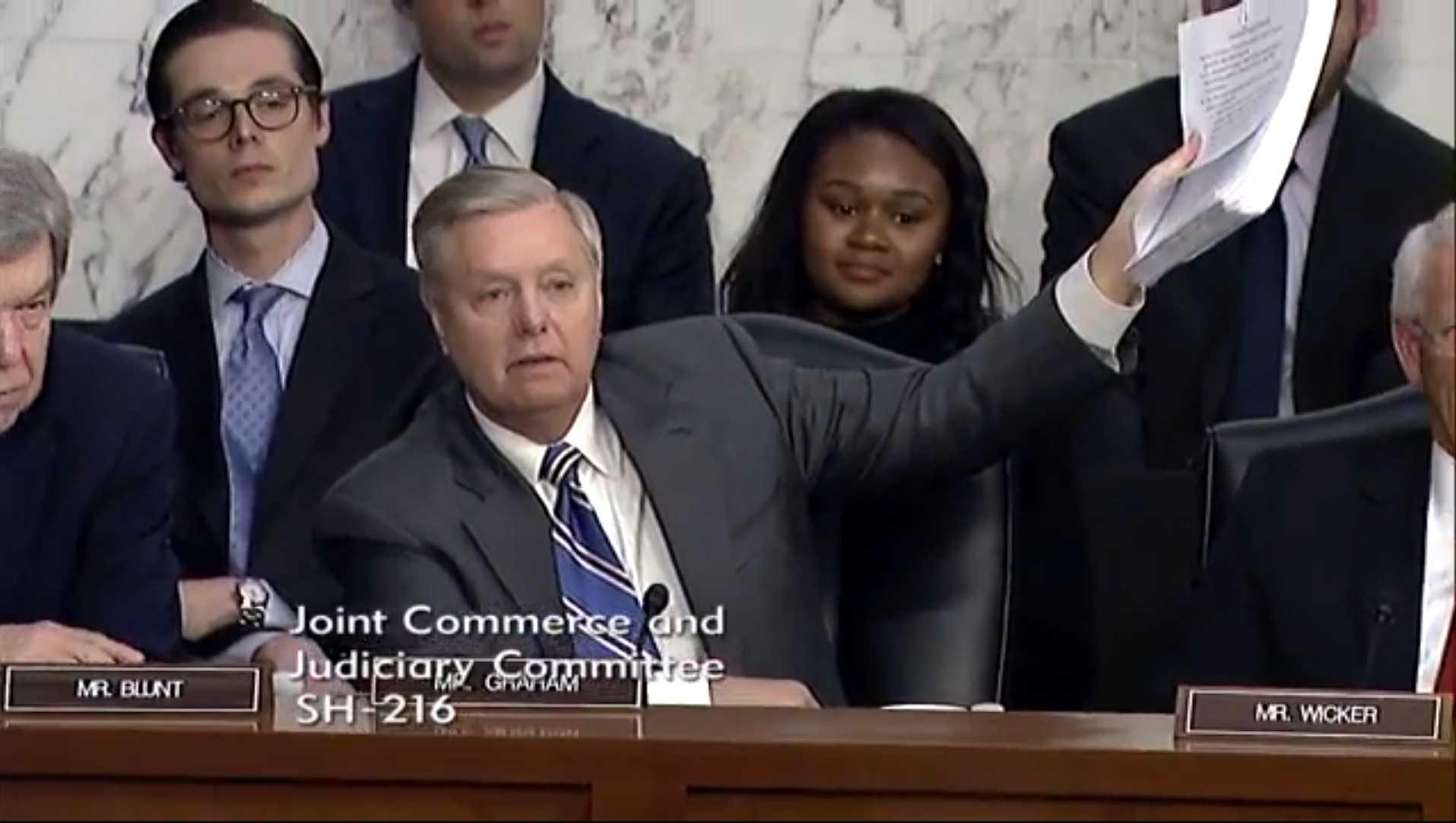 Senator Graham hält einen dicken Stapel Papier hoch