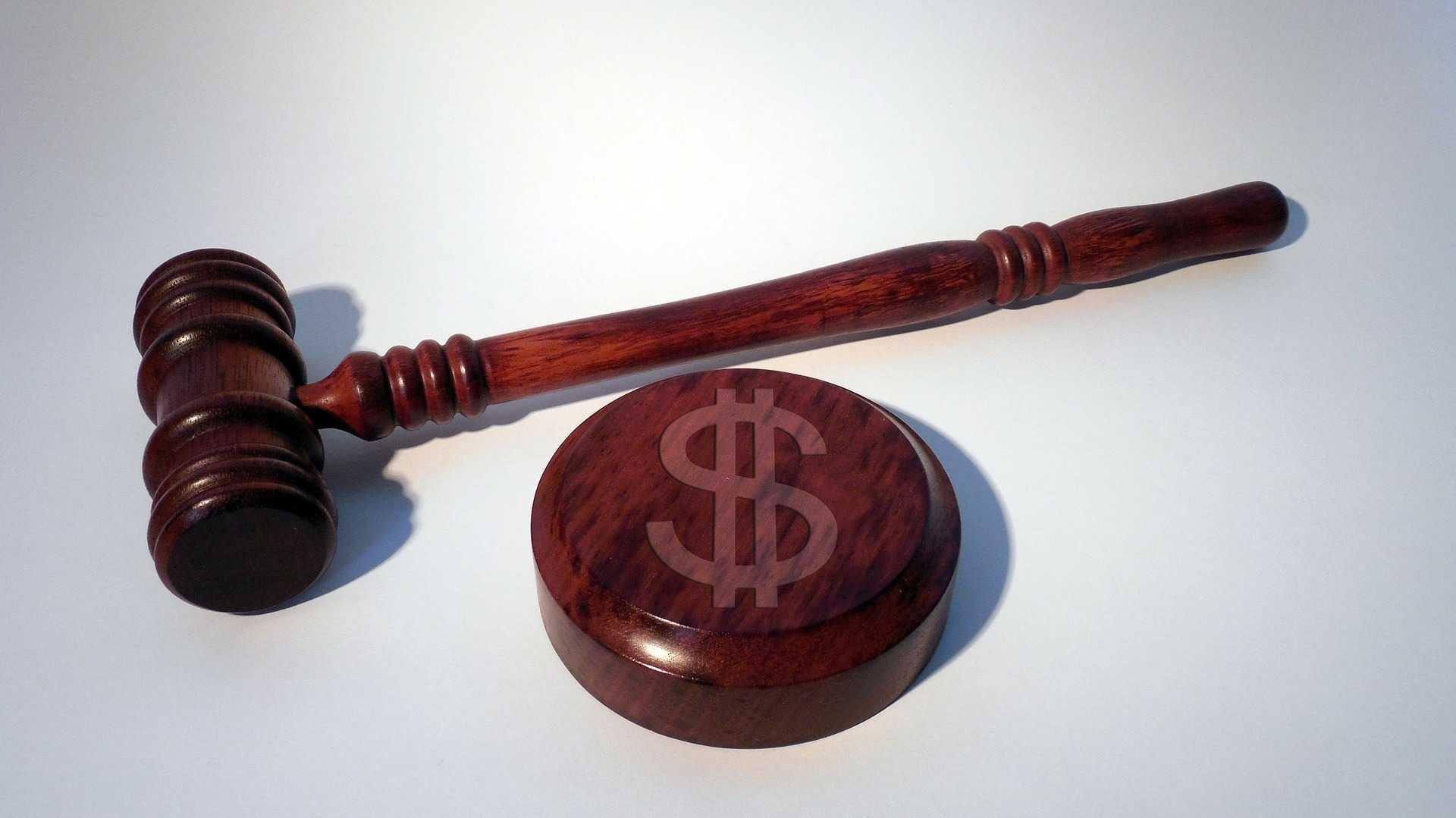 Richterhammer neben Resonanzblock mit Dollarzeichen