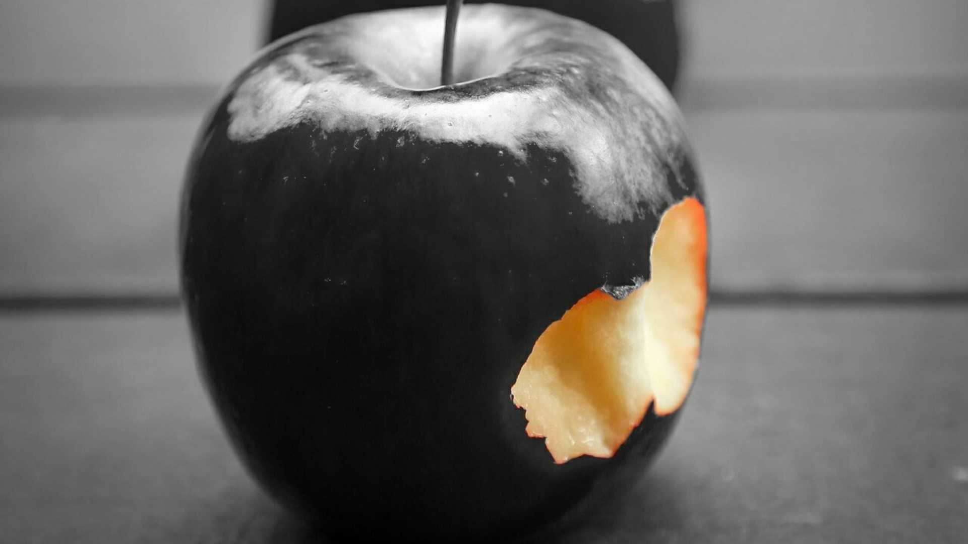 Angebissener schwarzer Apfel
