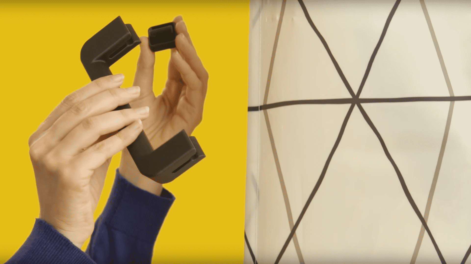 Zwei Hände halten Teile von einem 3D-gedruckten Griff neben einen Duschvorhang.