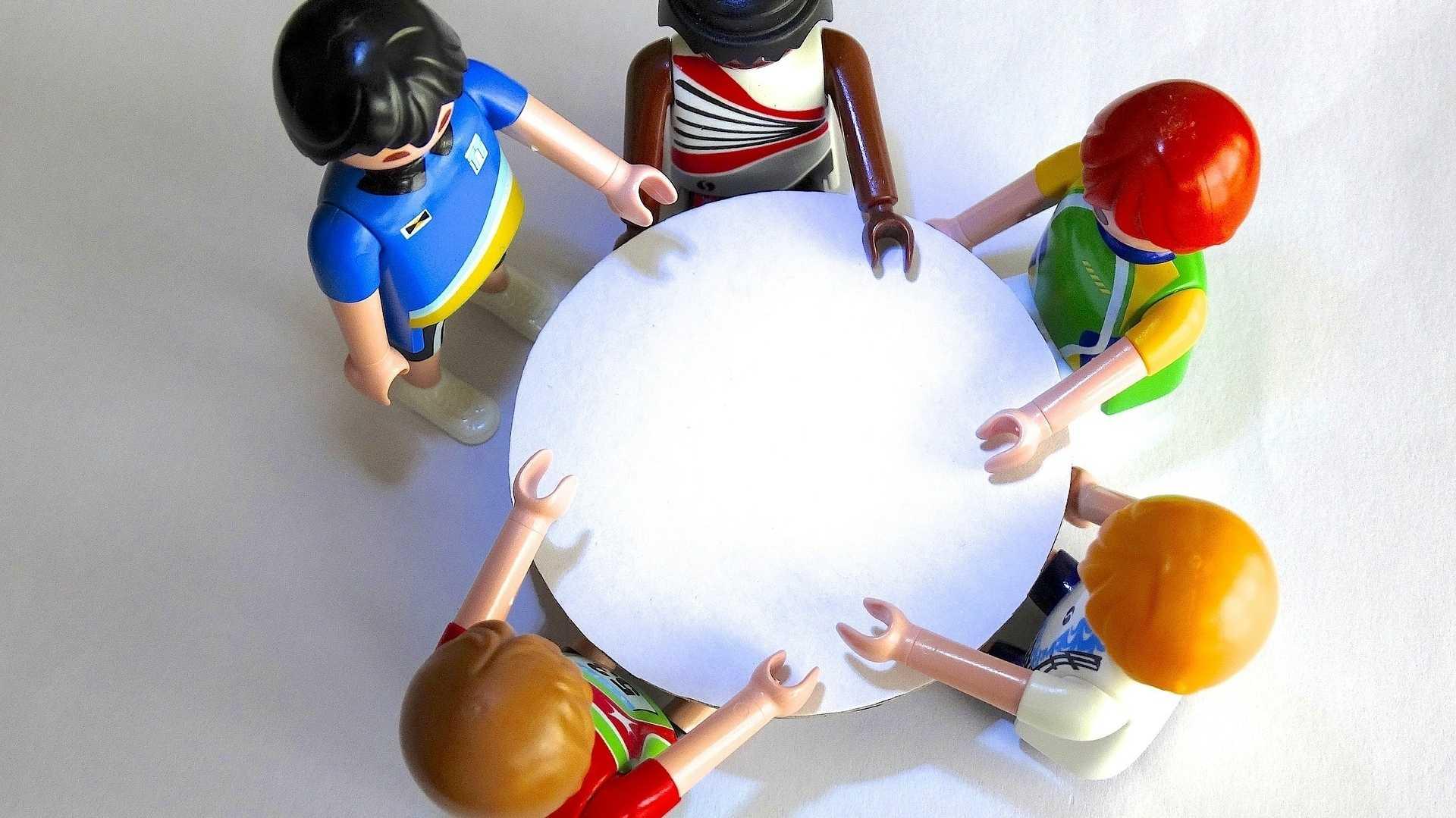 5 Playmobil-Figuren um einen runden Tisch