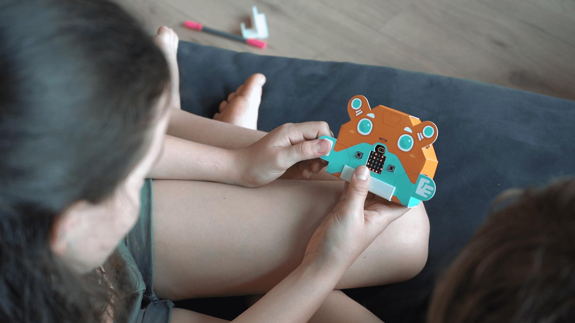 Zwei Kinder blicken auf einen bunten Papproboter mit LED-Matrix im Bauch.